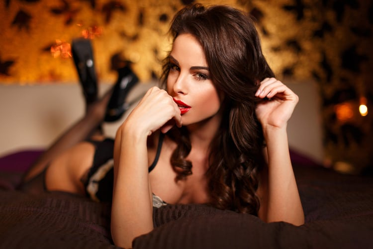 Seductive woman laying in bed with legs crossed